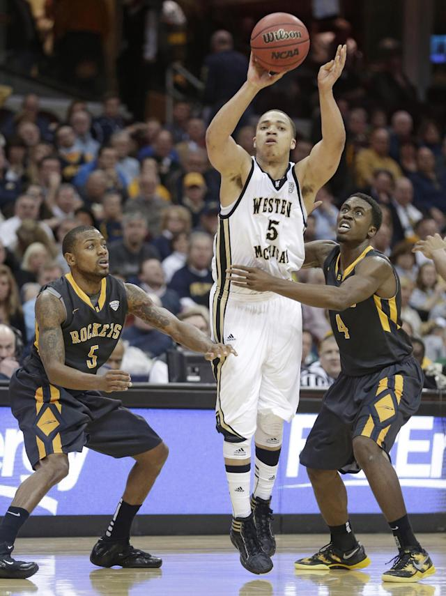 Western Michigan's David Brown, center, shoots between Toledo's Rian Pearson, left, and Justin Drummond during the second half of an NCAA college basketball championship game at the Mid-American Conference tournament on Saturday, March 15, 2014, in Cleveland. Western Michigan defeated Toledo 98-77. (AP Photo/Tony Dejak)