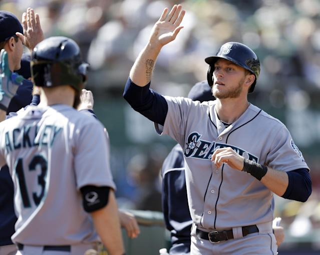 Seattle Mariners' Michael Saunders, right, is congratulated after scoring against the Oakland Athletics in the tenth inning of a baseball game Wednesday, May 7, 2014, in Oakland, Calif. Saunders scored on a hit by Justin Smoak. (AP Photo/Ben Margot)