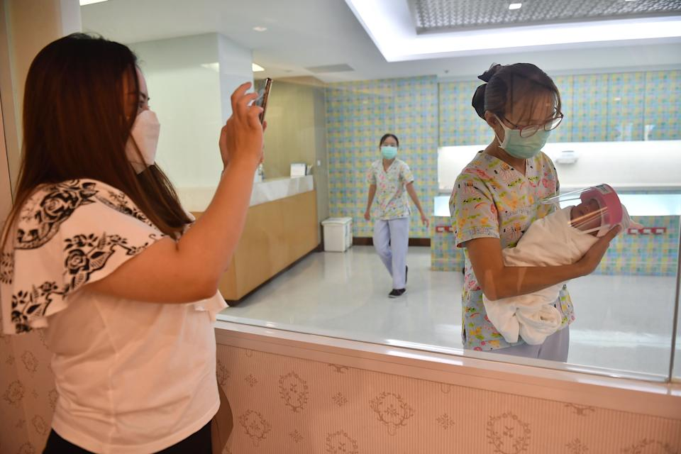 A mother takes a photo of her newborn baby (R) who is wearing a face shield, in an effort to halt the spread of the COVID-19 coronavirus, at Praram 9 Hospital in Bangkok on April 9, 2020. (Photo by Lillian SUWANRUMPHA / AFP) (Photo by LILLIAN SUWANRUMPHA/AFP via Getty Images)
