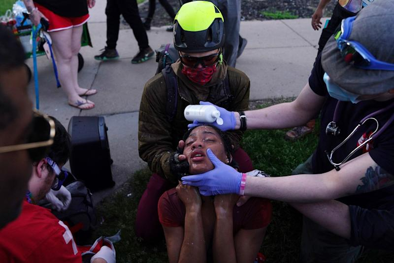 Citizen medics help a protester clear her eyes in Minneapolis as police moved in aggressively with tear gas to clear a group of protesters.