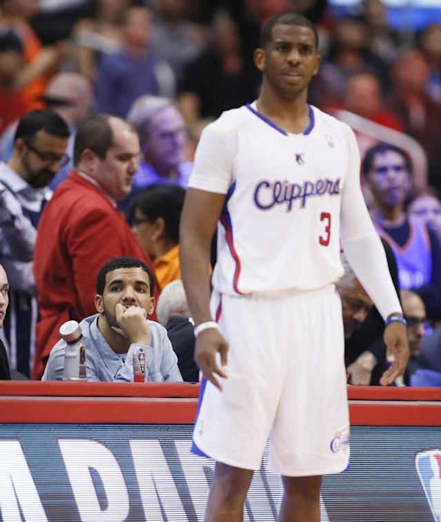 Recording artist Drake watches while Los Angeles Clippers guard Chris Paul stands on the court in front of him during the NBA basketball game between the Oklahoma City Thunder and Los Angeles Clippers in Los Angeles, Wednesday, April 9, 2014. (AP Photo/Danny Moloshok)