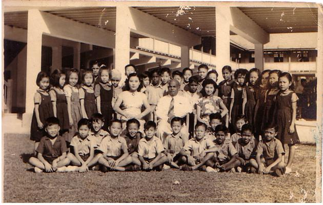 C Kunalan's primary three class photo in 1951. Kunalan, who was from Pasir Panjang English School, is the boy standing between the principal and teacher wearing a floral cheongsam.
