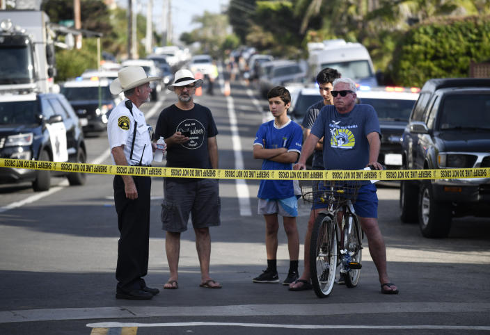 Residents wait behind police tape on the street above the site of a cliff collapse at a popular beach Friday, Aug. 2, 2019, in Encinitas, Calif. At least one person was reportedly killed, and multiple people were injured, when an oceanfront bluff collapsed Friday at Grandview Beach in the Leucadia area of Encinitas, authorities said. (AP Photo/Denis Poroy)