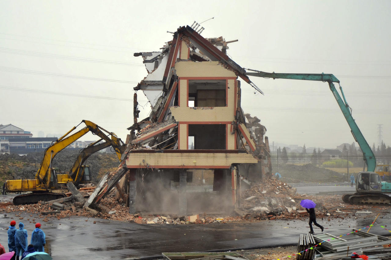 A house in the middle of a new road is being torn down on the outskirts of Wenling city, in eastern China's Zhejiang province, Saturday, Dec. 1, 2012. Authorities have demolished the five-story home that stood incongruously in the middle of the new main road and had become the latest symbol of resistance by Chinese homeowners against officials accused of offering unfair compensation. (AP Photo) CHINA OUT