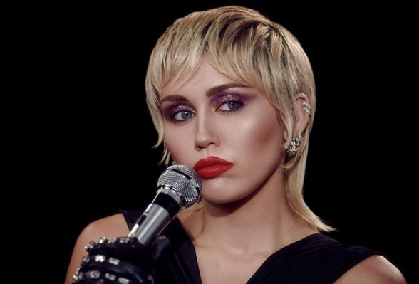 """Miley Cyrus in a promotional photo for her new single, """"Midnight Sky"""". She has a blonde mullet, red lipstick, purple eyeshadow and is holding a silver microphone"""