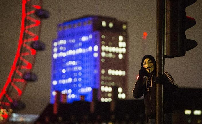 """An anti-capitalist protester wearing a Guy Fawkes mask stands on a traffic light during the """"Million Masks March"""" organised by the group Anonymous, near the London Eye in London on November 5, 2015 (AFP Photo/Jack Taylor)"""