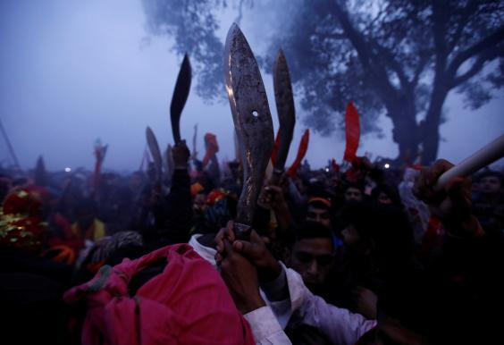 Devotees raise their sacrificial blades at the sacrificial ceremony (REUTERS)