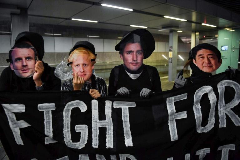 Protesters wearing masks of French President Emmanuel Macron, British Prime Minister Boris Johnson, Canadian Prime Minister Justin Trudeau and Japan's Prime Minister Shinzo Abe at a rally at Tamar Park in Hong Kong (AFP Photo/Lillian SUWANRUMPHA)