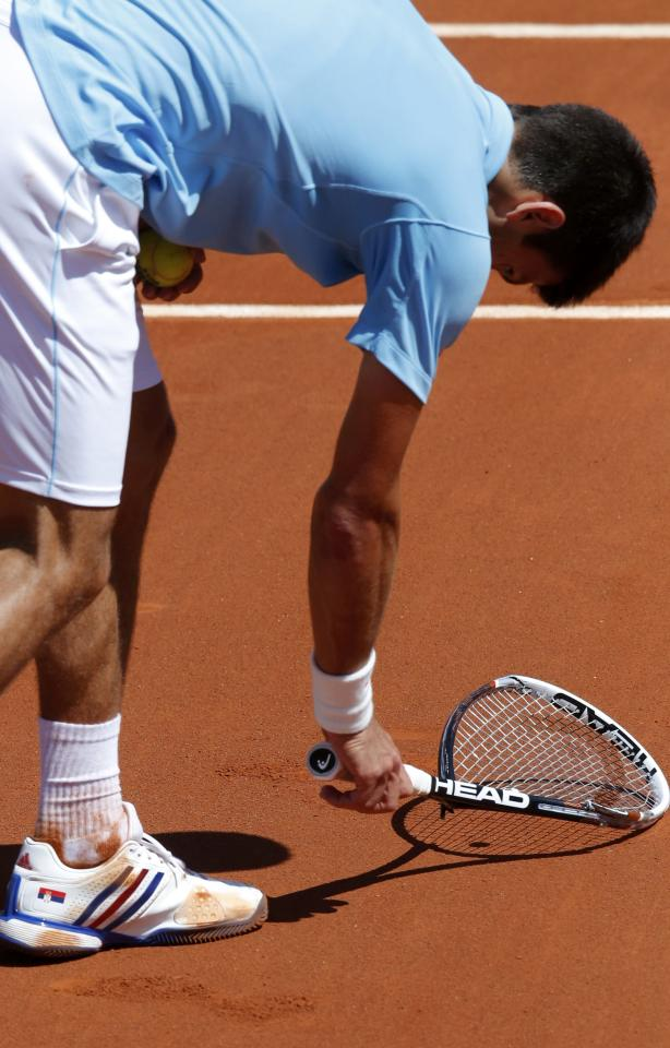 Novak Djokovic of Serbia picks up his broken racket after he smashed it during his men's semi-final match against Ernests Gulbis of Latvia at the French Open tennis tournament at the Roland Garros stadium in Paris June 6, 2014. REUTERS/Jean-Paul Pelissier (FRANCE - Tags: SPORT TENNIS)
