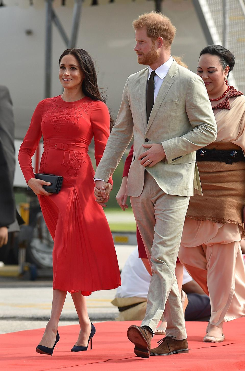 <p>The Duke and Duchess of Sussex arrived in Tonga on October 25 and Meghan dressed her bump in a red Self-Portrait dress for the occasion – a sartorial tribute to the country's flag. She accessorised the look with a navy pair of Manolo Blahniks. <em>[Photo: Getty]</em> </p>