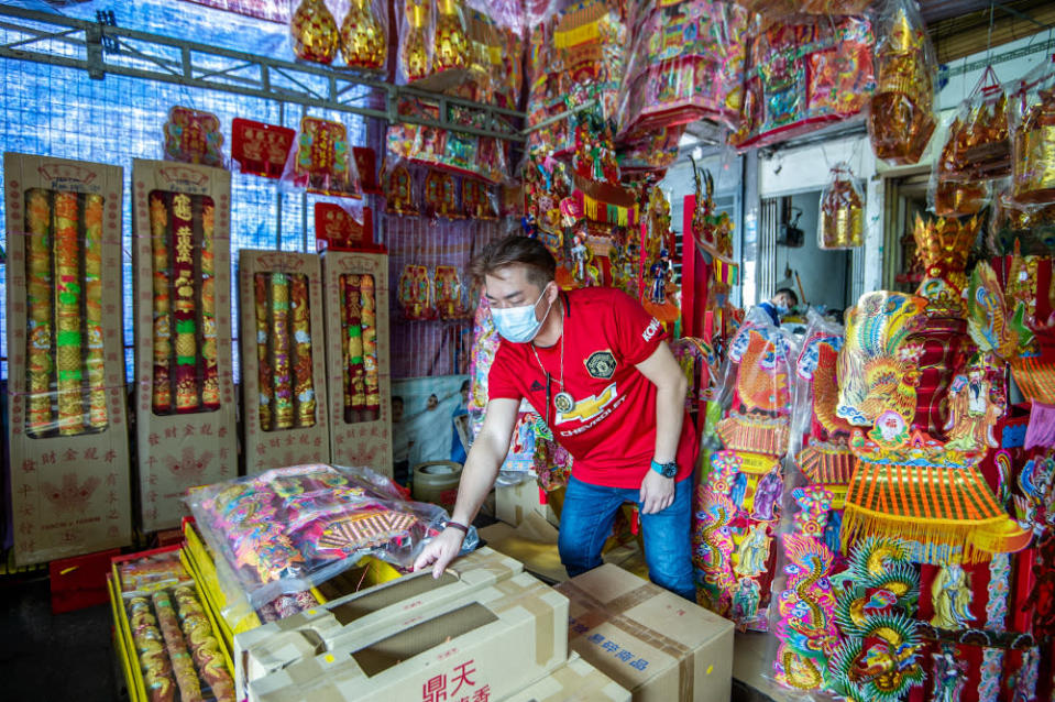 Religious goods store Feng Long Trading owner Sam Ying Meng arranges prayer items at his shop for the annual Bai Tian Gong festivities (Hokkien New Year eve) on the 9th day of the Lunar calendar (February 20). — Picture by Shafwan Zaidon