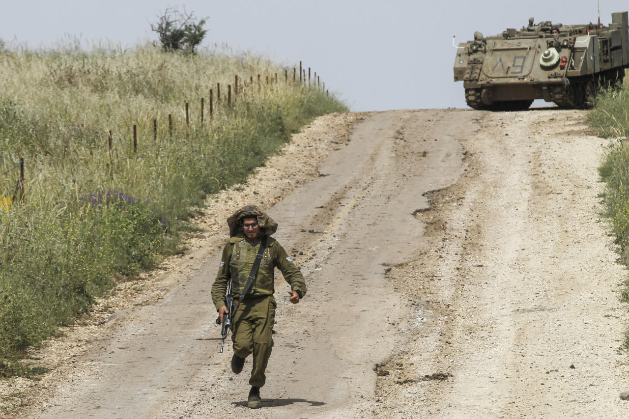 <p>An Israeli soldier runs to direct a M113 armored personal vehicle near the Syrian border in the Israel-annexed Golan Heights on May 10, 2018. Israel's army said today it had carried out widespread raids against Iranian targets in Syria overnight after rocket fire towards its forces it blamed on Iran, marking a sharp escalation between the two enemies. Israel carried out the raids after it said around 20 rockets, either Fajr or Grad type, were fired from Syria at its forces in the occupied Golan Heights at around midnight. (Photo: Jalaa Marey/AFP/Getty Images) </p>