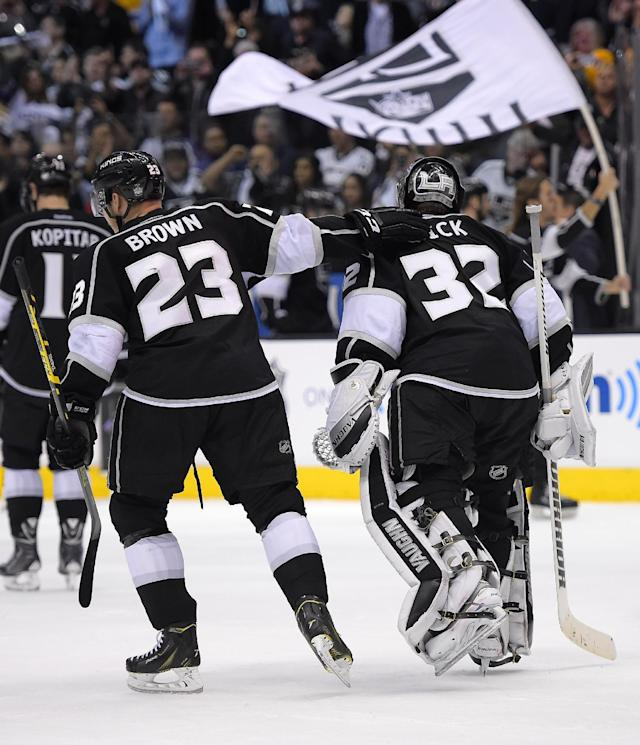 Los Angeles Kings right wing Dustin Brown, left, and goalie Jonathan Quick skate off the ice after the Kings defeated the San Jose Sharks in Game 6 of an NHL hockey first-round playoff series, Monday, April 28, 2014, in Los Angeles. The Kings won 4-1. (AP Photo)