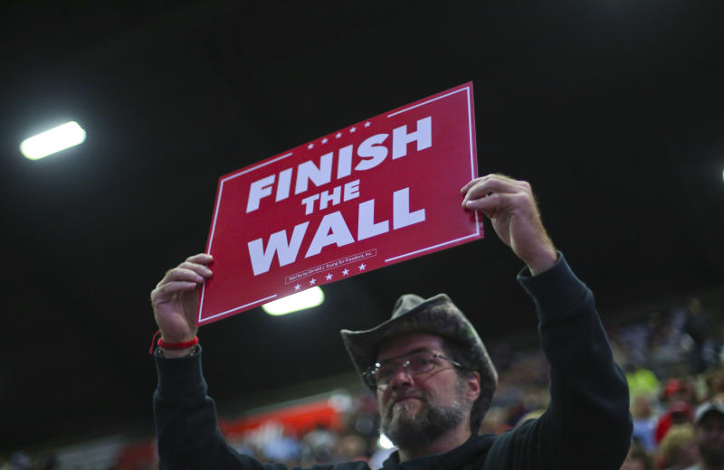 "A supporter holds up a sign which reads, ""FINISH THE WALL"" as he waits to hear President Donald Trump speak at a campaign rally at WesBanco Arena, Saturday, Sept. 29, 2018, in Wheeling, W.Va. (AP Photo/Pablo Martinez Monsivais)"
