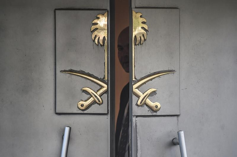 A Saudi official looks through the door of the Saudi Arabian consulate in Istanbul during a demonstration for missing journalist Jamal Khashoggi