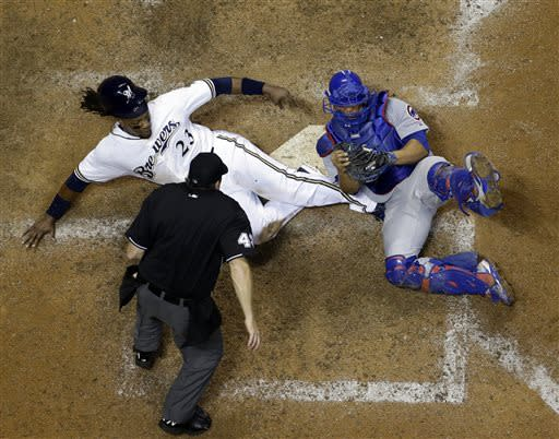 Chicago Cubs catcher Welington Castillo holds on to the ball after tagging out Milwaukee Brewers' Rickie Weeks during the ninth inning of a baseball game Wednesday, June 26, 2013, in Milwaukee. Weeks tried to score from third on a ball hit by Yuniesky Betancourt. The Cubs won 5-4. (AP Photo/Morry Gash)