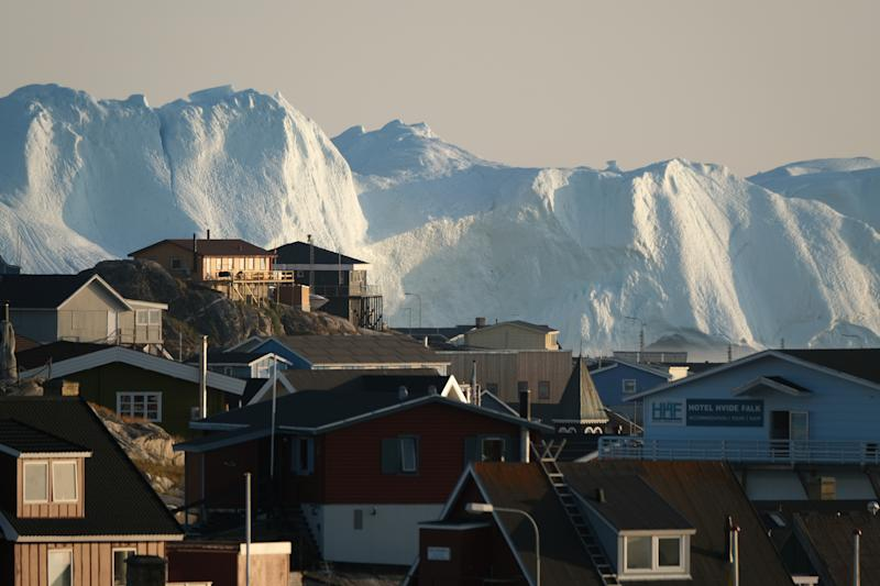 Icebergs in the Ilulissat Icefjord loom behind buildings in Ilulissat, Greenland. (Photo: Sean Gallup/Getty Images)