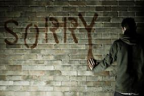 Man standing hand placed on wall at word sorry written on wall.