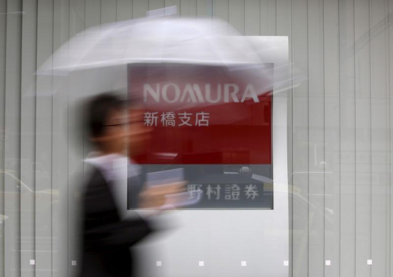 A man holding an umbrella walks in front of a signboard of Nomura Securities outside its branch in Tokyo