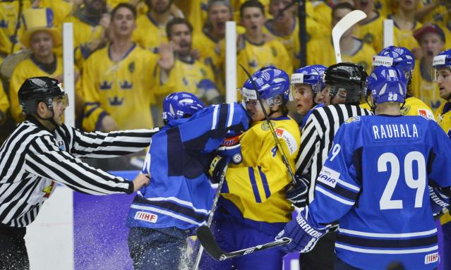 Finland's Rasmus Ristolainen (2nd L) hits Sweden's Robert Hagg during their IIHF World Junior Championship Group B preliminary round ice hockey match at Malmo Arena in Malmo, December 28, 2013. REUTERS/Ludvig Thunman/TT News Agency (SWEDEN - Tags: SPORT ICE HOCKEY) ATTENTION EDITORS - THIS IMAGE HAS BEEN SUPPLIED BY A THIRD PARTY. IT IS DISTRIBUTED, EXACTLY AS RECEIVED BY REUTERS, AS A SERVICE TO CLIENTS. SWEDEN OUT. NO COMMERCIAL OR EDITORIAL SALES IN SWEDEN. NO COMMERCIAL SALES