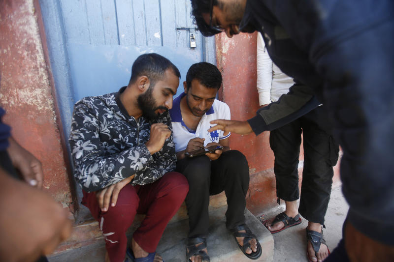 Support staff play games on a cell phone inside the premises of a school deserted school compound in Srinagar, Indian controlled Kashmir, Monday, Aug. 19, 2019. Restrictions continue in much of Indian-administered Kashmir, despite India's government saying it was gradually restoring phone lines and easing a security lockdown that's been in place for nearly two weeks. (AP Photo/Mukhtar Khan)