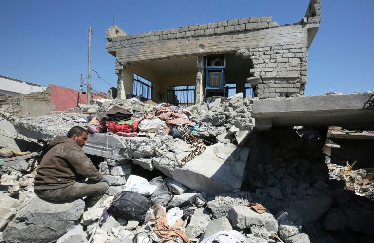 An Iraqi man in the rubble of destroyed houses in Mosul's al-Jadida area on March 26, 2017, after air strikes which reportedly killed civilians
