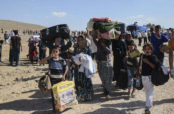 Syrian Kurds carry their belongings after crossing into Turkey near the southeastern town of Suruc in Sanliurfa province, on September 19, 2014 (AFP Photo/Ilyas Akengin)