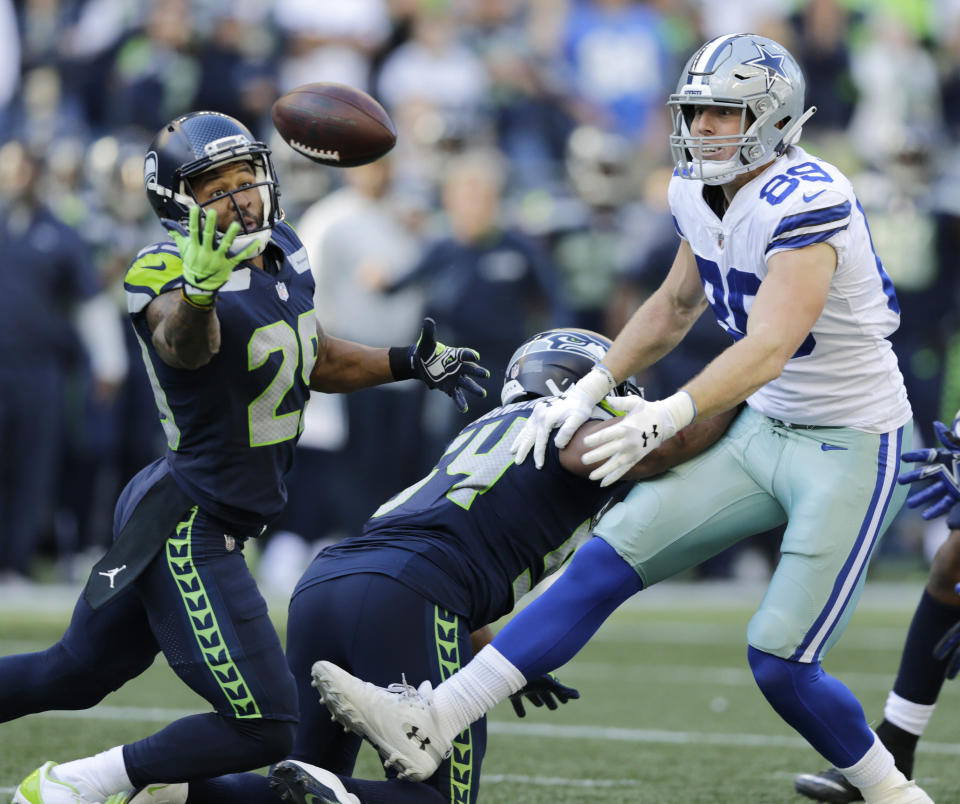 <p>Seattle Seahawks free safety Earl Thomas, left, reaches for a pass he intercepted that was intended for Dallas Cowboys tight end Blake Jarwin, right, as Seahawks' Bobby Wagner, center, looks on during the second half of an NFL football game, Sunday, Sept. 23, 2018, in Seattle. The pick was Thomas' second of the game. (AP Photo/John Froschauer) </p>