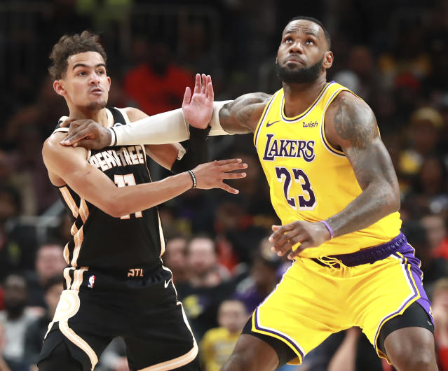 Los Angeles Lakers forward LeBron James, right, pushes Atlanta Hawks guard Trae Young out of the way as he prepares to grab a jump ball during the second half of an NBA basketball game Sunday, Dec. 15, 2019, in Atlanta. (Curtis Compton/Atlanta Journal-Constitution via AP)