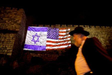 A man walks by as the Israeli national flag and an American one are projected on a part of the walls surrounding Jerusalem's Old City December 6, 2017. REUTERS/Ronen Zvulun/Files
