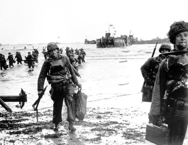 <p>Carrying full equipment, American assault troops move onto a beachhead code-named Omaha Beach on the northern coast of France on June 6, 1944, during the Allied invasion of the Normandy coast. (Photo: AP) </p>