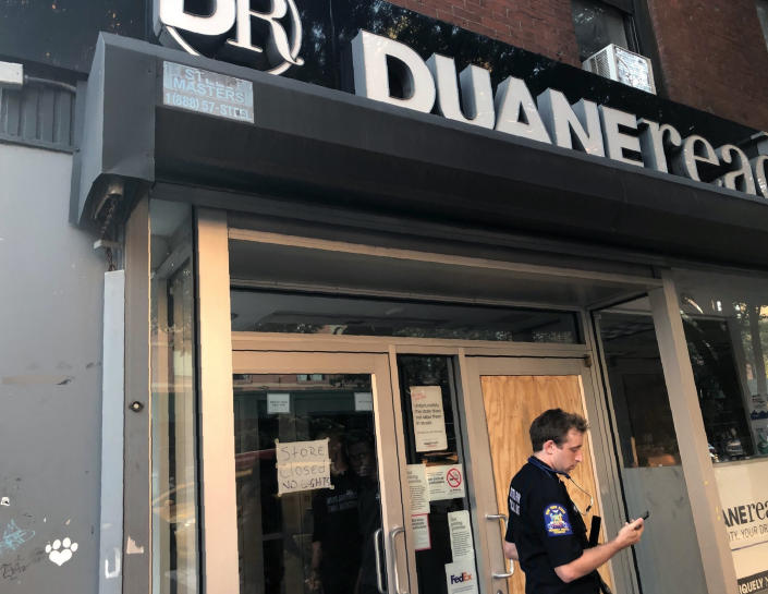 A New York State Emergency Medical Technician looks at his mobile phone while standing in front of a Duane Reade store that closed after loosing power, Saturday, July 13, 2019, in New York.  (Photo: Leezel Tanglao/AP)