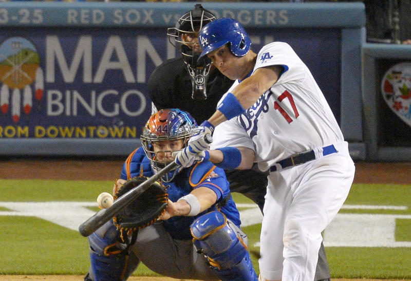 Los Angeles Dodgers' A.J. Ellis, right, hits an RBI single as New York Mets catcher John Buck, left, looks on along with home plate umpire Jeff Kellogg during the sixth inning of their baseball game, Tuesday, Aug. 13, 2013, in Los Angeles. (AP Photo/Mark J. Terrill)