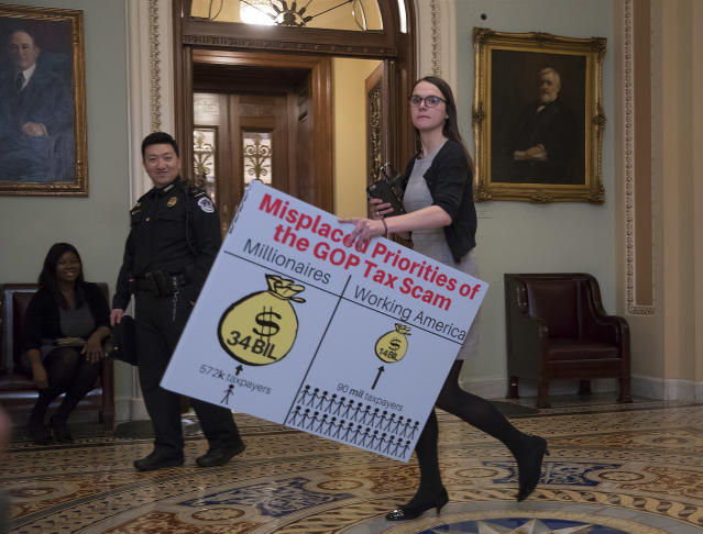 <p>A Democratic aide carries a chart past the Senate chamber to be used by the minority to argue against the Republican tax bill, on Capitol Hill in Washington, Friday night, Dec. 1, 2017. (Photo: J. Scott Applewhite/AP) </p>