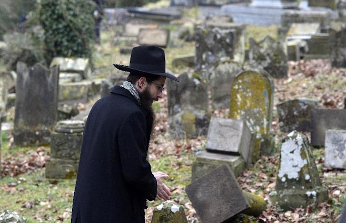 A member of the Jewish community looks at broken tombstones on February 17, 2015 following the desecration of around 300 tombs in Sarre-Union, eastern France (AFP Photo/Patrick Hertzog)