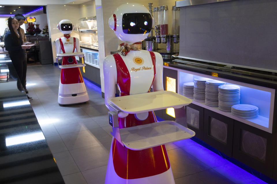 Leah Hu, left, and her brother Leon demonstrate the use of robots for serving purposes or for dirty dishes collection, as part of a tryout of measures to respect social distancing and help curb the spread of the COVID-19 coronavirus, at the family's Royal Palace restaurant in Renesse, south-western Netherlands, Wednesday, May 27, 2020. (AP Photo/Peter Dejong)