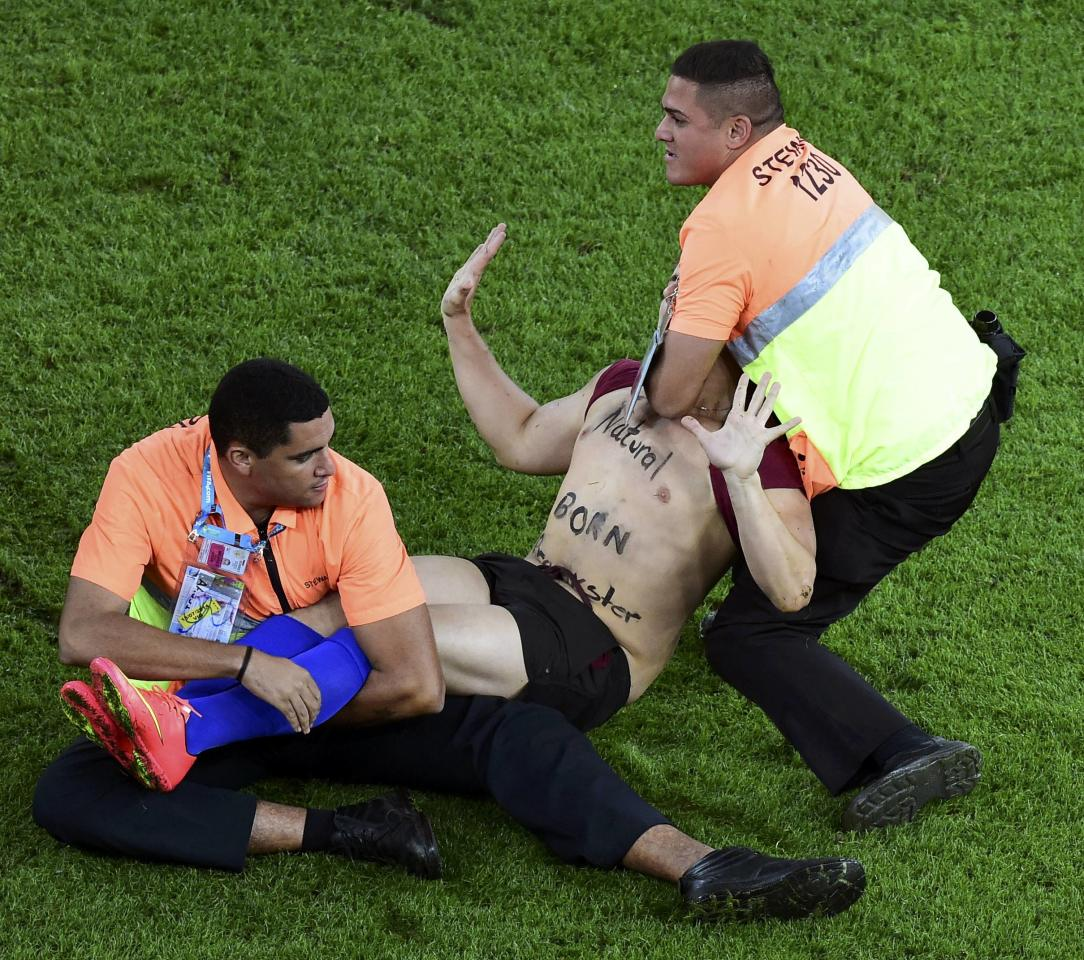 Security guards grab a fan who ran onto the pitch during the 2014 World Cup final between Germany and Argentina at the Maracana stadium in Rio de Janeiro July 13, 2014. REUTERS/Francois Xavier Marit (BRAZIL - Tags: SOCCER SPORT WORLD CUP TPX IMAGES OF THE DAY)