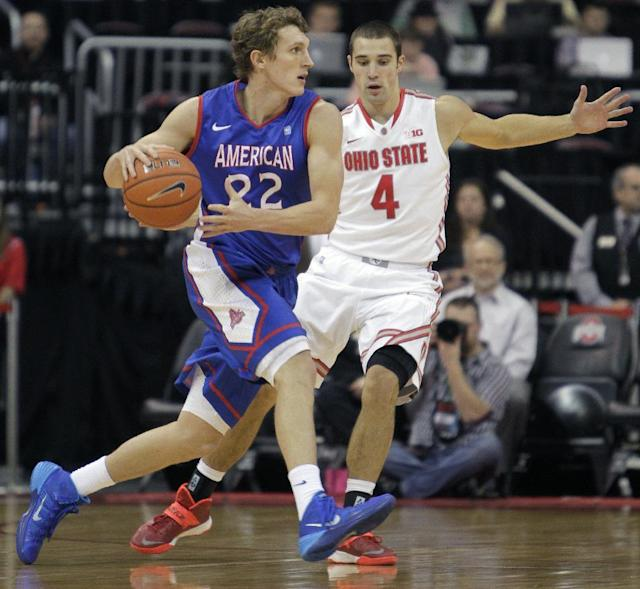 """FILE - This Nov. 20, 2103 file photo shows American University's John Schoof, left, guarded by Ohio State's Aaron Craft during the first half of an NCAA college basketball game in Columbus, Ohio. From Princeton to American by way of Georgetown with a guard named """"Peewee,"""" Mike Brennan has the Eagles unbeaten in the Patriot League in his first season at the school. (AP Photo/Jay LaPrete, File)"""