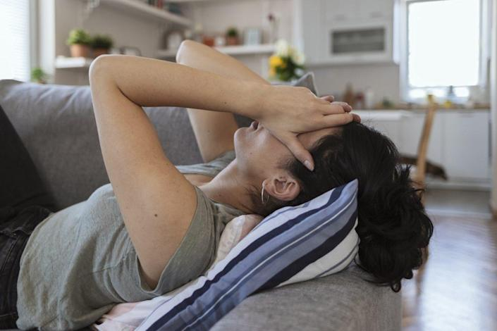 Tired woman holding her head with her hands.