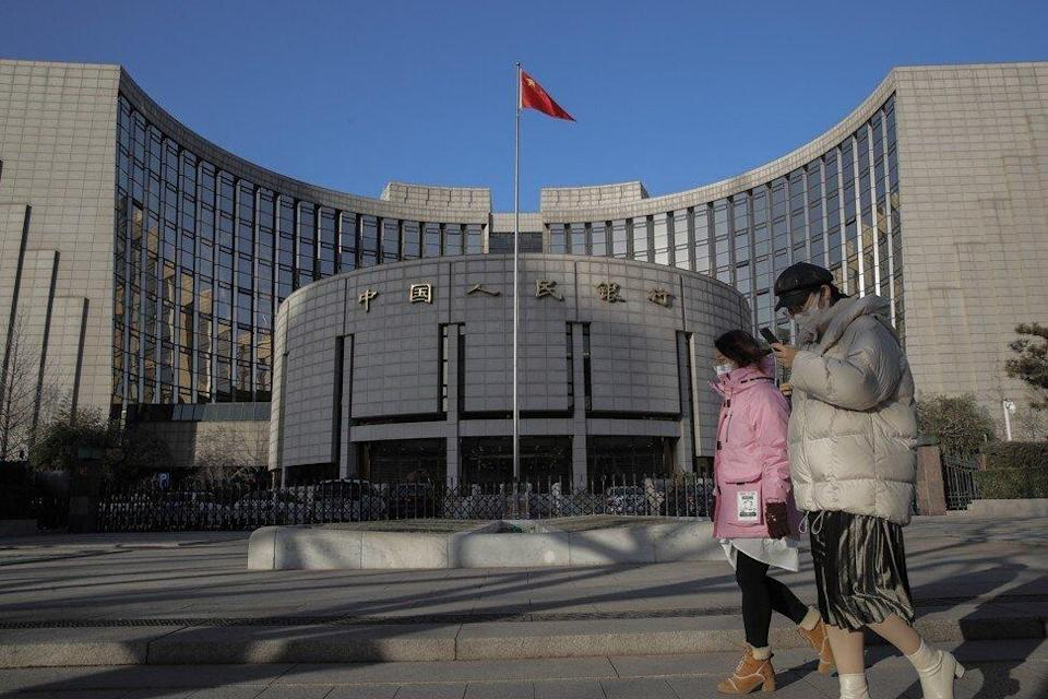People wearing protective face masks walk past the People's Bank of China in Beijing. Photo: EPA-EFE