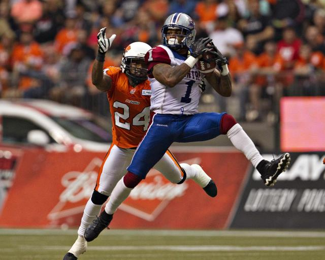 Montreal Alouettes slotback Bruce Arland catches a pass for the first down as BC Lions linebacker Korey Banks (L) moves in behind during the first half of their CFL football game in Vancouver, British Columbia September 15, 2013. REUTERS/Andy Clark (CANADA - Tags: SPORT FOOTBALL)