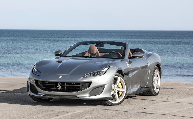 A silver Ferrari Portofino, a sleek front-engined convertible sports car, parked on a beach.