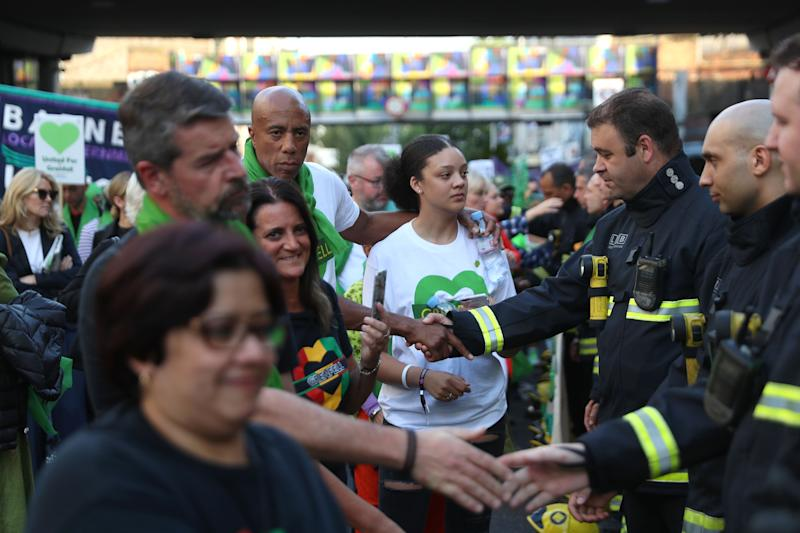 Firefighters greet local residents on the one year anniversary of the Grenfell Tower fire (Picture: Getty)