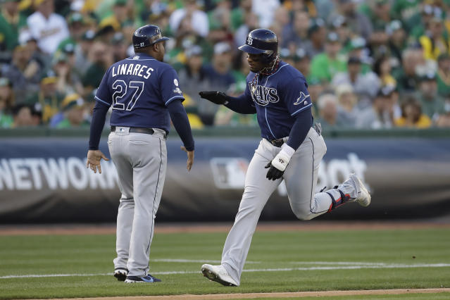 Tampa Bay Rays' Yandy Diaz, right, is congratulated by third base coach Rodney Linares after hitting a solo home run against the Oakland Athletics during the first inning of an American League wild-card baseball game in Oakland, Calif., Wednesday, Oct. 2, 2019. (AP Photo/Ben Margot)