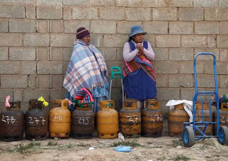 Women line up with gas canisters next to blocked petrol plant of Senkata in El Alto outskirts of La Paz