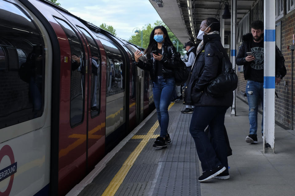 Commuters, some wearing protective masks to protect against coronavirus stand on the platform at Leytonstone underground station, in London, Monday, May 18, 2020. Britain's Prime Minister Boris Johnson announced last Sunday that people could return to work if they could not work from home. (AP Photo/Alberto Pezzali)