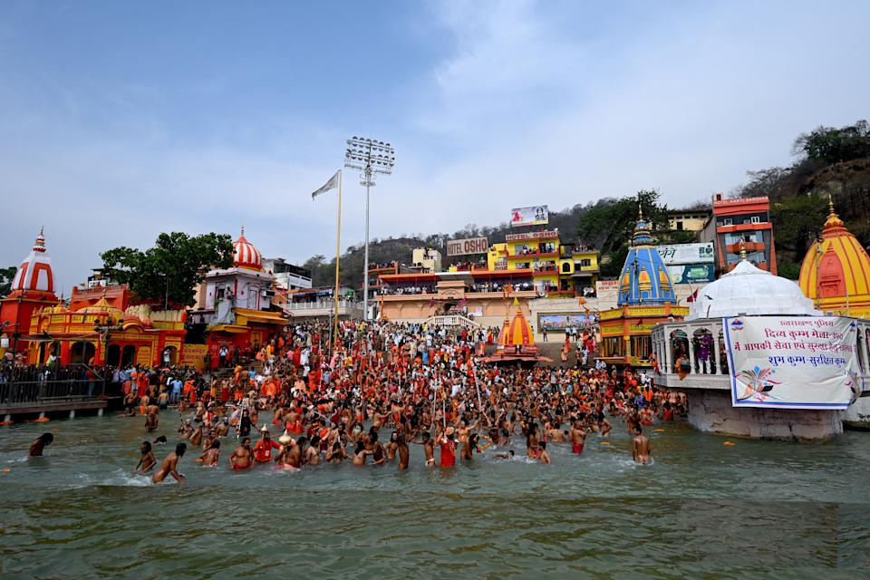 Naga Sadhus (Hindu holy men) take a holy dip in the waters of the Ganges River on the day of Shahi Snan (royal bath) during the ongoing religious Kumbh Mela festival, in Haridwar on April 12, 2021. (Photo by Money SHARMA / AFP) (Photo by MONEY SHARMA/AFP via Getty Images)