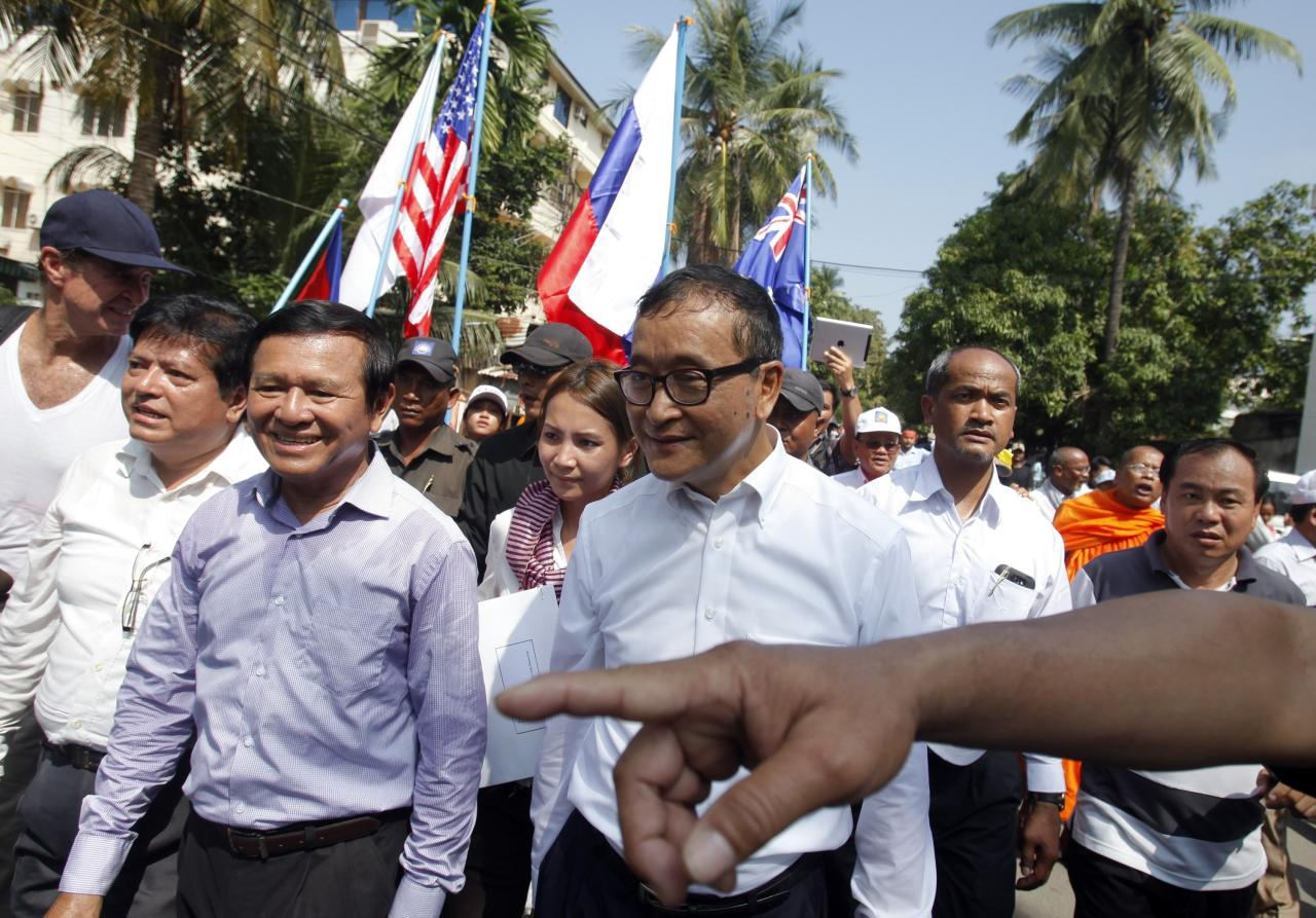 Sam Rainsy (C), president of the opposition Cambodia National Rescue Party (CNRP), marches along a street to the French, British and U.S. Embassy during a protest in central Phnom Penh October 24, 2013. The CNRP began on Wednesday a three-day mass demonstration over a disputed national election, which extended the long serving Prime Minister Hun Sen's rule for another five years. Hundreds of supporters lead by Rainsy marched to foreign embassies to push for an independent probe into the July 28 polls. REUTERS/Samrang Pring (CAMBODIA - Tags: POLITICS CIVIL UNREST ELECTIONS)