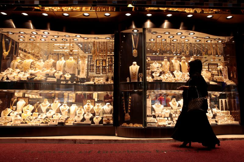 FILE PHOTO: A woman walks past gold jewellery displayed in a shop window at the Gold Souq in Dubai