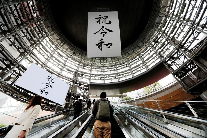 FILE PHOTO: A huge banner and screen celebrating Reiwa, Japan's new imperial era, are displayed on the first day of the Emperor Naruhito's accession to the throne at a business district in Tokyo